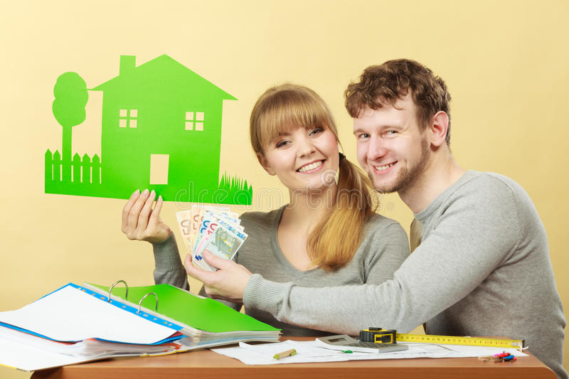 Couple with house and money. Home real estate credit mortgage concept. Couple with house and money. Young men and women counting banknotes and holding cartboard stock photos