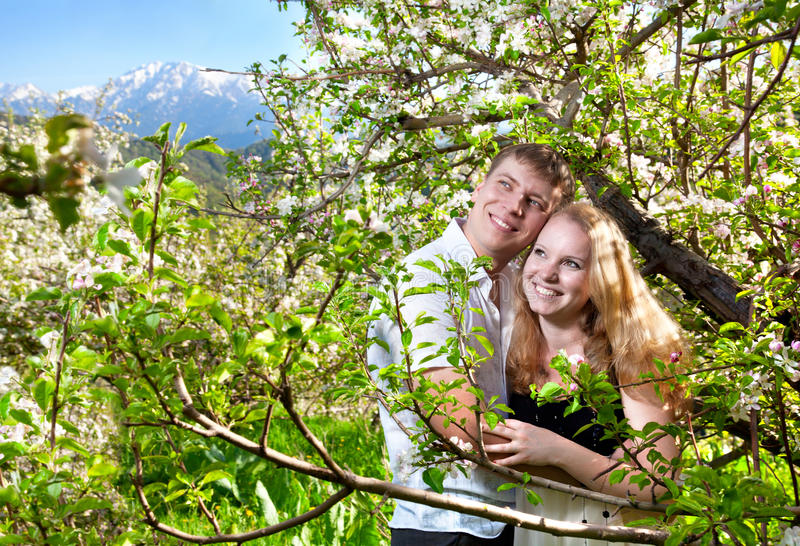 Couple hugging around bloomy trees. Beautiful couple smiling and hugging around bloomy apple trees at mountain background stock photo