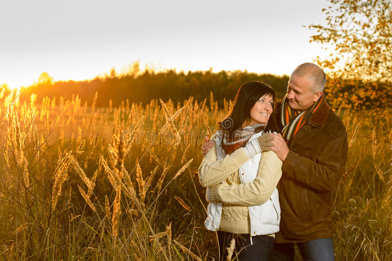 Couple hugging during autumn sunset countryside. Romantic couple hugging during autumn sunset countryside looking at each other stock image