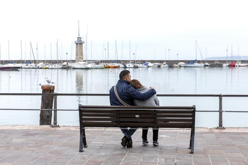 Couple hugging on a bench. Young couple sitting on a wooden bench.  royalty free stock images