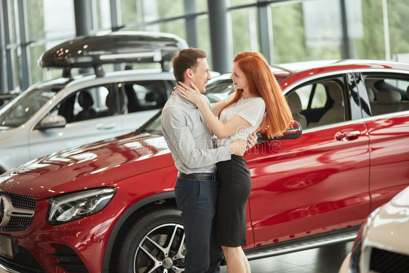 Couple hugging while buying first new family car together in dealership. royalty free stock photos