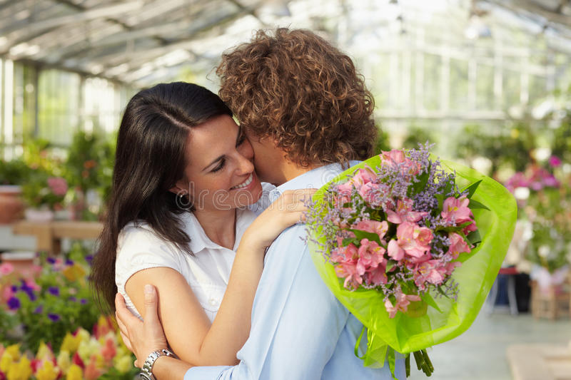 Couple hugging in flower nursery. Mid adult couple hugging in flower nursery and holding bouquet stock image