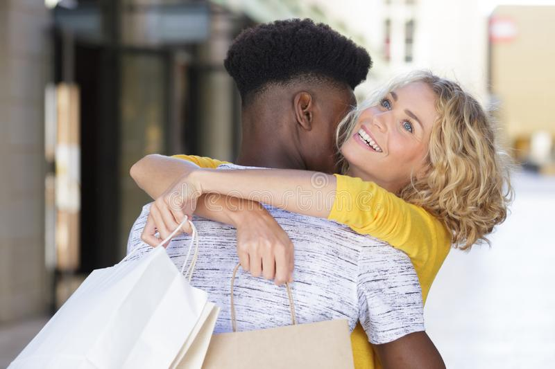 Couple hugging and holding shopping bags stock photo