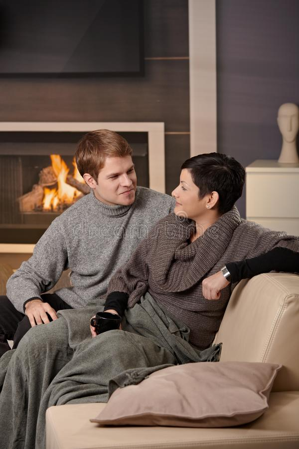 Couple hugging home. Young couple hugging on sofa in front of fireplace at home, looking at each other, smiling royalty free stock image