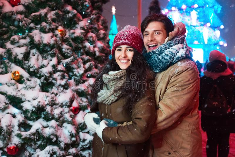 Couple Hugging Next To Decorated Christmas Tree In Night City royalty free stock photography