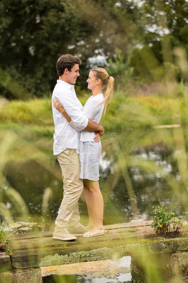Couple hugging pier stock images