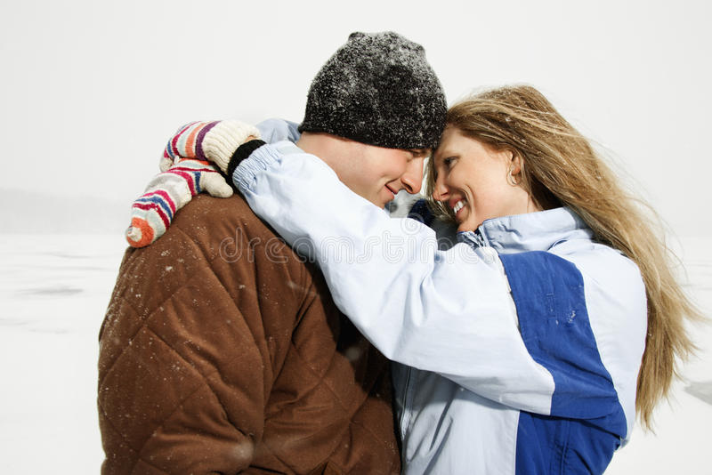 Couple Hugging in Snow. Young adult couple smiling at each other and in a close embrace in a winter environment. Horizontal shot royalty free stock image