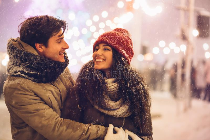 Couple Hugging Standing On A Street Decorated With Winter Lights stock photos