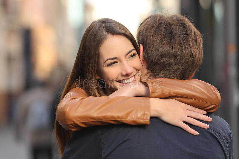 Couple hugging in the street. Portrait of a happy couple hugging in the street with the women face in foreground