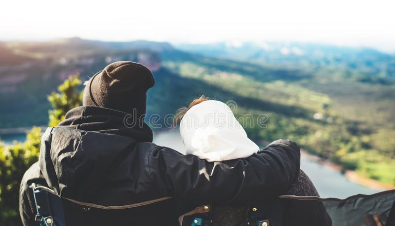 Couple hugging two romantic people cuddling and looking panoramic landscape of sun flare mountain, travelers weekend concept stock photography