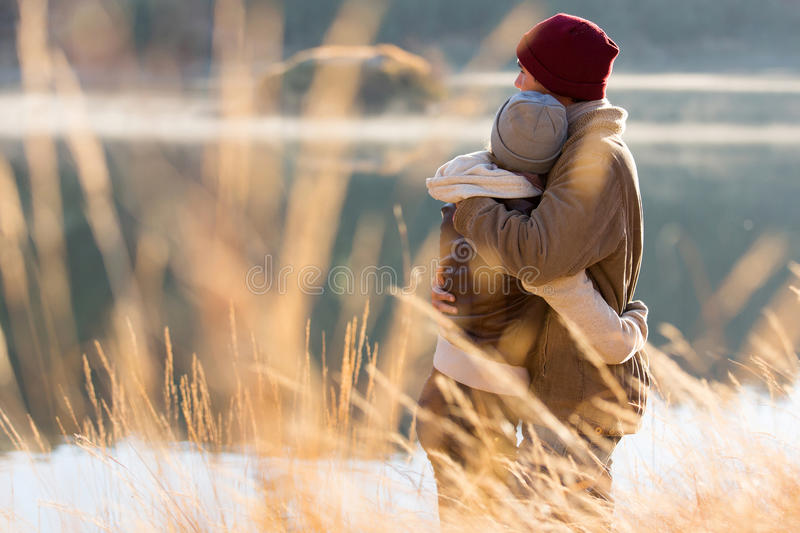 Couple hugging winter. Back view of lovely young couple hugging in winter