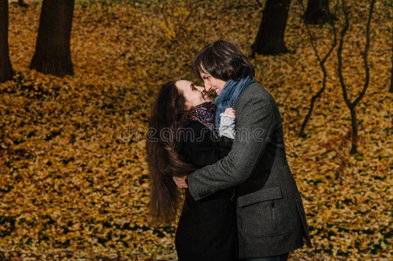 Couple hugs in a fall park. Golden Autumn on the background with leaves and trees, foliage. Wear coats and jeans, long hair. women smiles ready to kiss, the royalty free stock photos