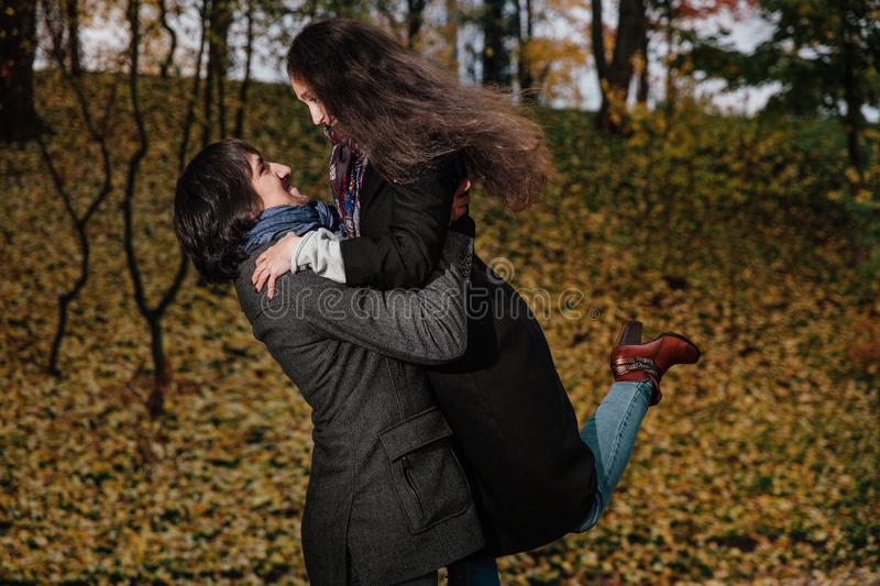 Couple hugs in a fall park. Golden Autumn on the background with leaves and trees, foliage. Wear coats and jeans, long hair. Holds on his hands stock photos