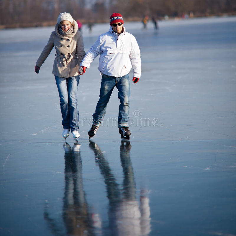 Couple ice skating on a pond stock photos