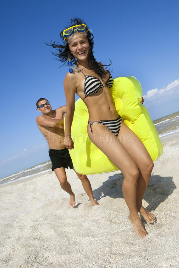 Couple with an inflatable beach mattress stock photos