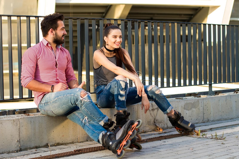 Couple on inline skates sitting. stock image