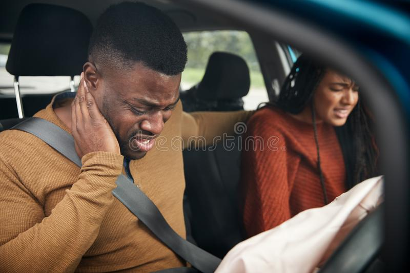 Couple Involved In Car Crash With Male Driver Suffering With Whiplash Injury stock images