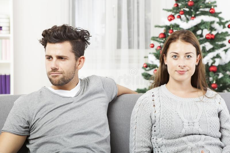 Couple is irritated of christmas. Young modern couple is irritated of christmas with christmas tree in background royalty free stock photography