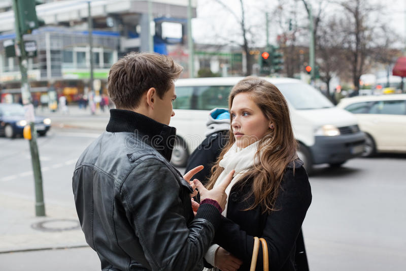 Couple In Jackets Communicating On Street Side. Young couple in jackets communicating on street side royalty free stock photos