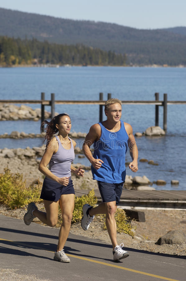 Couple Jogging By Lake stock photography