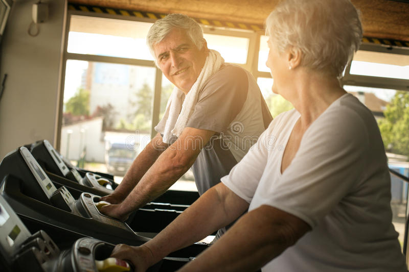 Couple on jogging machine. Senior couple workout in the g royalty free stock photos