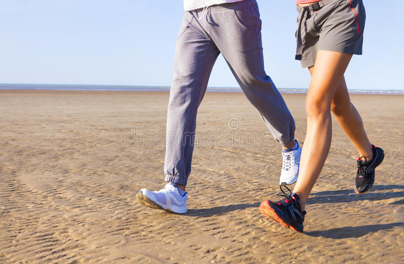 Couple jogging outside, runners training outdoors working out. In nature against blue sky with sunset light. Close up stock photography