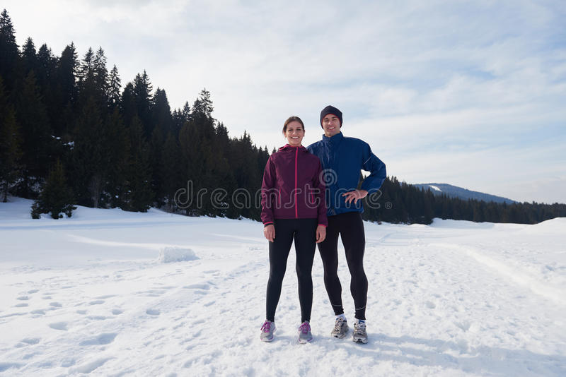 Couple jogging outside on snow. Healthy young couple jogging outside on snow in forest. athlete running on beautiful sunny winter day royalty free stock photo