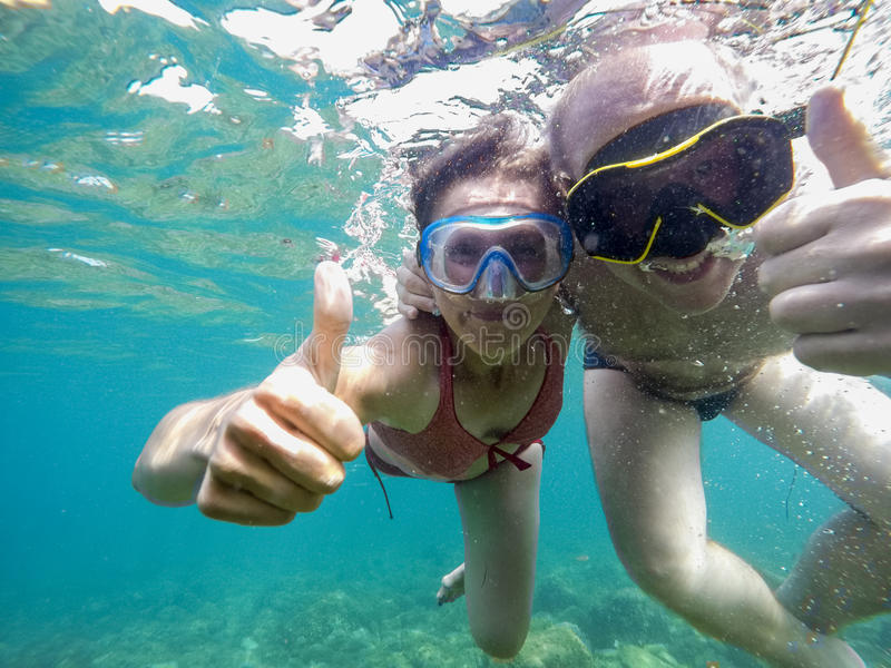 Couple joyfully swimming underwater in sea stock photos