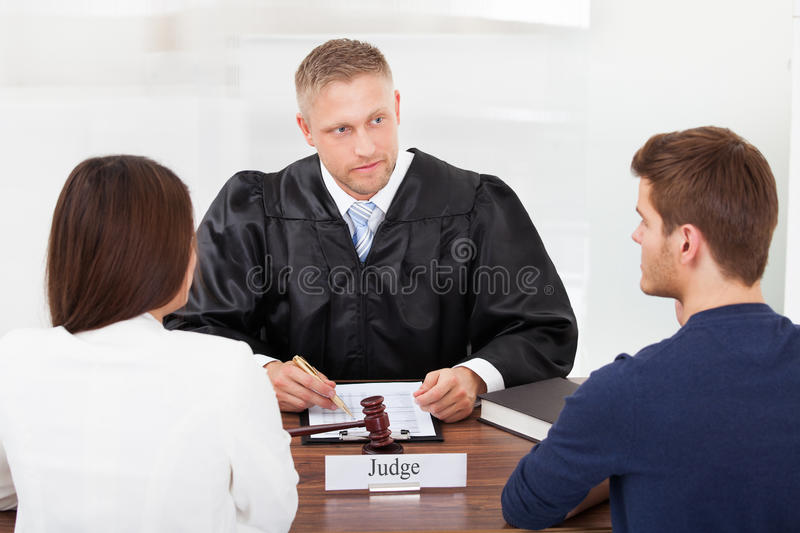 Couple with judge in court. Rear view of couple with judge writing at desk in court stock image