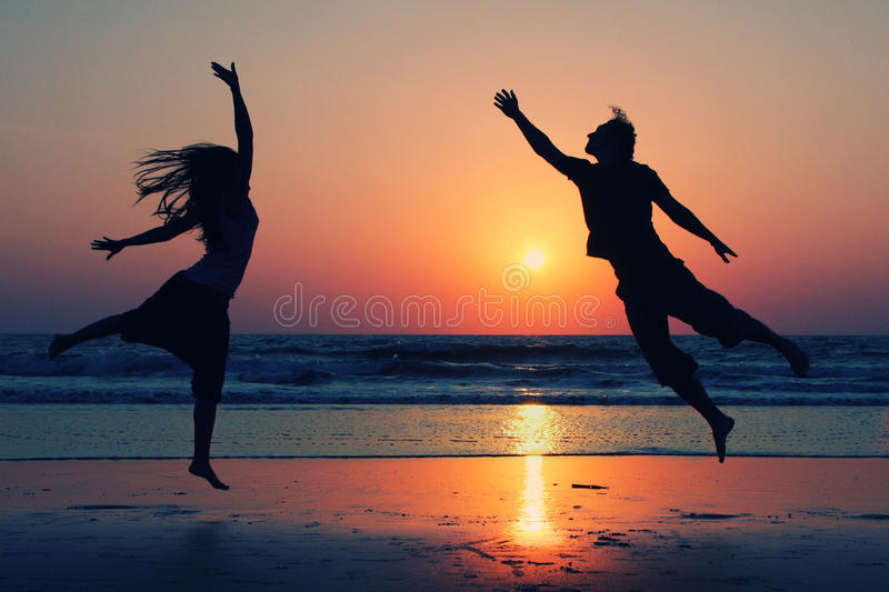Couple jumping on background of lake at sunset stock photos