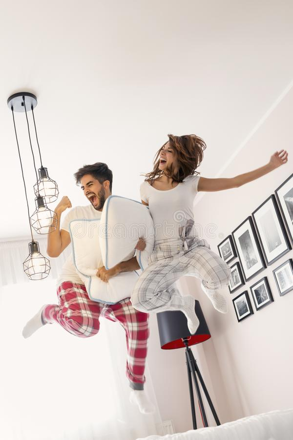 Couple jumping on bed royalty free stock photography