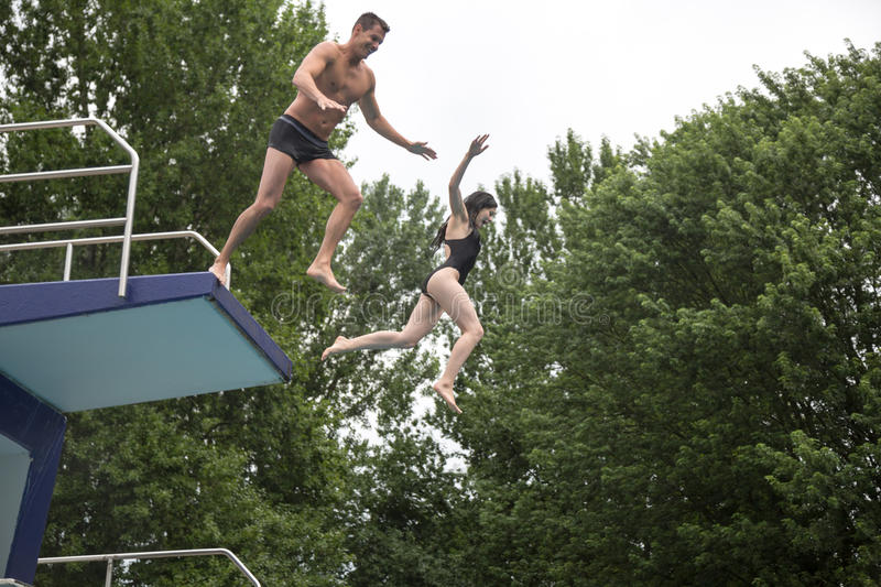 Couple jumping from a diving board into a swimming. A couple jumping off a diving platform into a public swimming pool royalty free stock photos