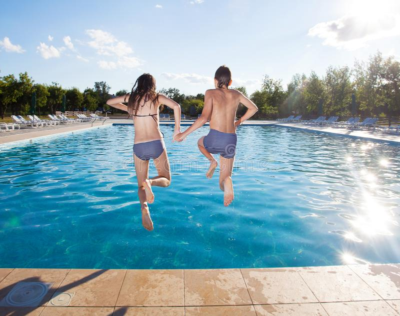 Couple jumping into pool. Summer vacations stock photography