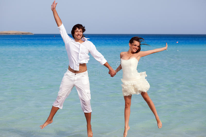 The couple is jumping in the sea. The smiling couple is jumping in the sea royalty free stock image