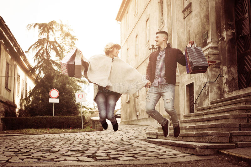 Couple jumping after shopping. stock photos