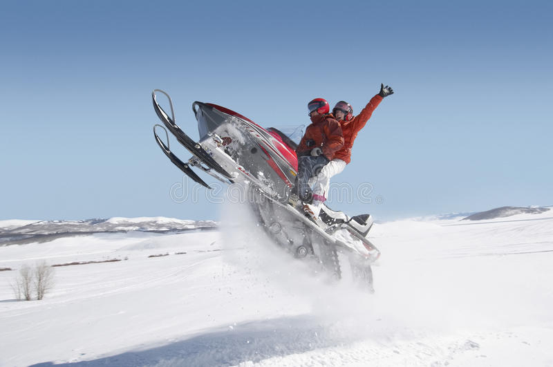 Couple Jumping Snowmobile In Snow royalty free stock images