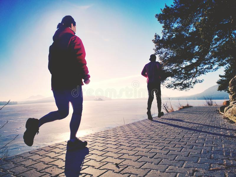 Couple jumping in the sun on a dock of lake. Happy people royalty free stock images