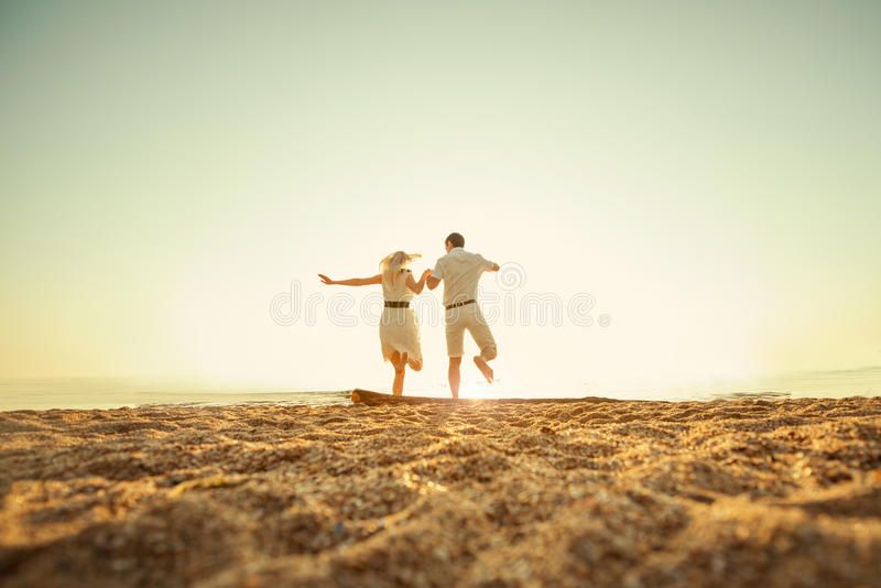 Couple jumping to the sea. At sunrise holding hands royalty free stock photography
