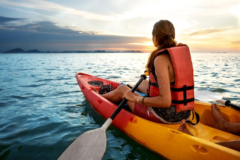 Couple kayaking together. Beautiful young couple kayaking on lake together and smiling at sunset royalty free stock image