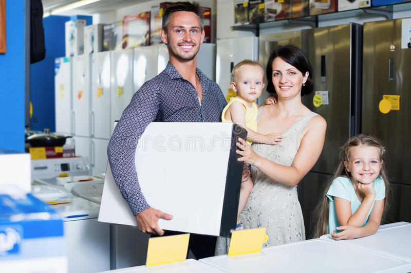 Couple with kids holding box with new electronics. Cheerful couple with two kids holding box with new electronics in household store royalty free stock image