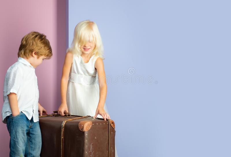 Couple kids with suitcase. Happy childhood. Boy and girl cute friends. Friendship and love. Lovely tender children royalty free stock photo