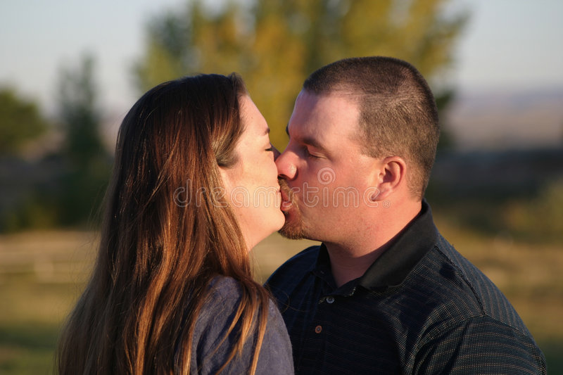 Couple Kiss. Touching photo of a couple kissing outdoors. The man is really planting one on the woman royalty free stock image
