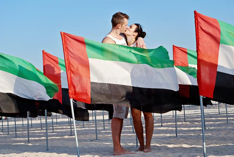 Couple kisses between flags of United Arab Emirates. United Arab Emirates Anniversary Celebration on the kite beach in Dubai. National day royalty free stock photography