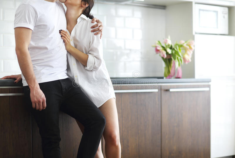 Couple kisses and hugs at kitchen in the morning. Young couple kisses and hugs at kitchen in the morning stock photos
