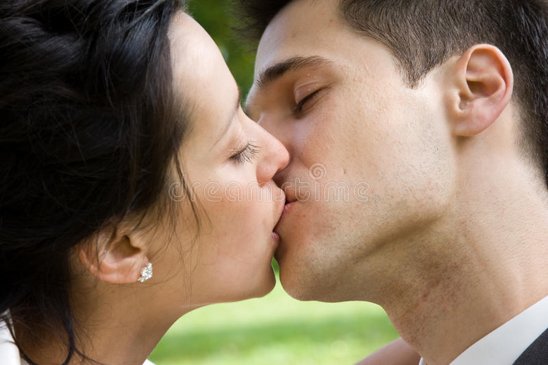 Couple kissing. Closeup of a couple kissing over the shoulder of the man royalty free stock photography