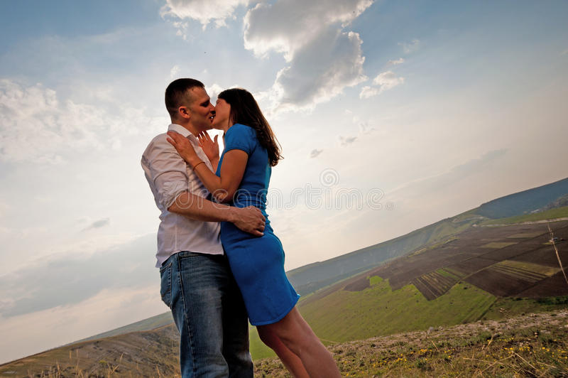 Couple kissing. Young attractive couple kissing against a landscape background stock image