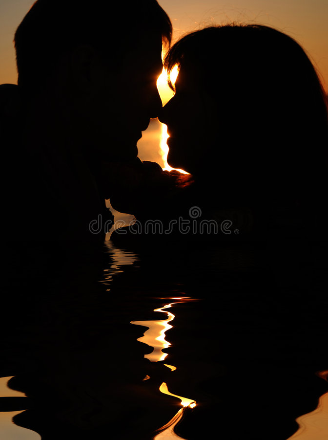 Couple kissing. Reflexion of couple kissing at sunset stock photo