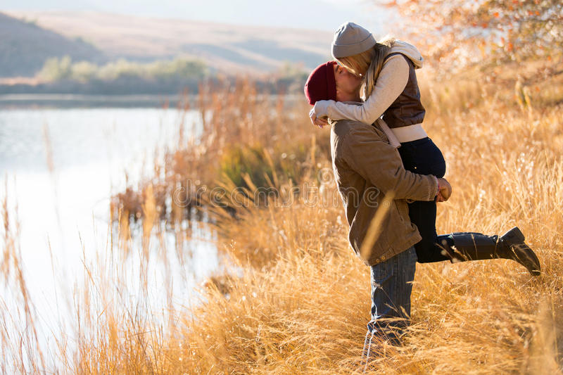 Couple kissing autumn. Lovely young couple kissing outdoors in autumn royalty free stock images