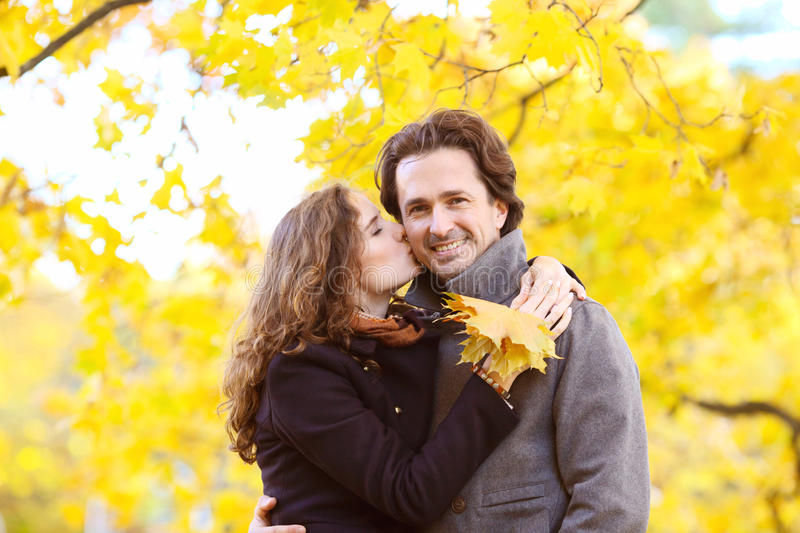 Couple kissing in autumn park royalty free stock photography