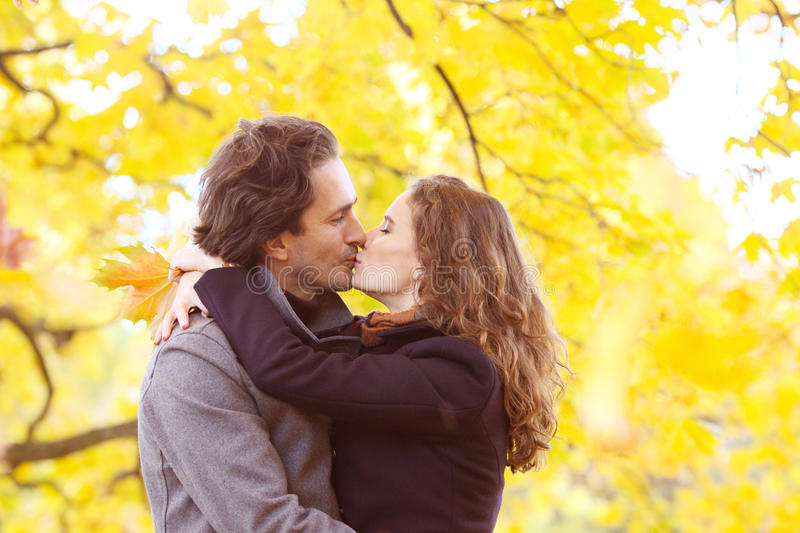 Couple kissing in autumn park royalty free stock photos